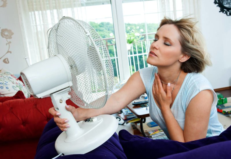 woman-cooling-herself-with-fan-800x553